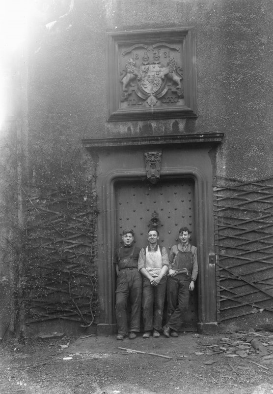 Detailed exterior view of the entrance doorway with three workmen standing in it seen from the West North West. Above the studded door is a stone relief of a coat-of-arms of two lions flanking a crest dated 1831 and with the initials TDL and CAC.