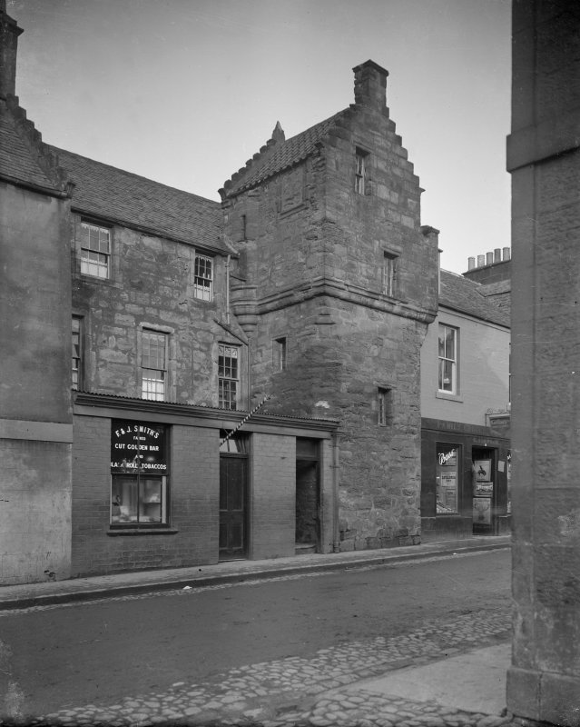 View from South West of Kellie Lodging, Pittenweem showing a window display for 'F & J Smith's famed Cut Golden Bar and Black Roll Tobaccos' and a family grocer shop