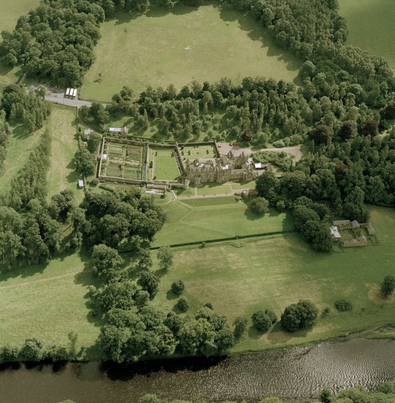 Oblique aerial view of Abbotsford centred on the country house with tea room, gardens and stables adjacent, taken from the NW.