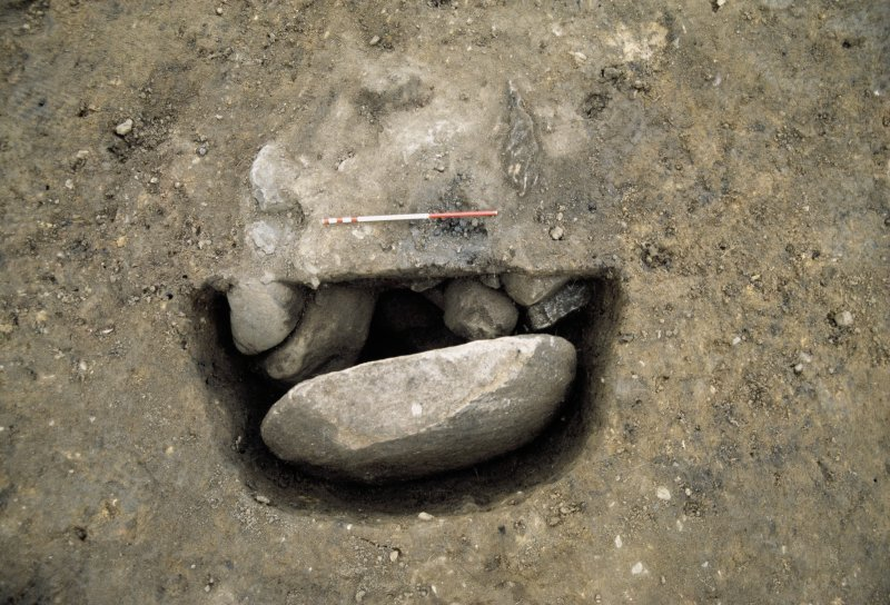 Excavation photographs: Posthole [688] with stone slab Find 5107 in situ.