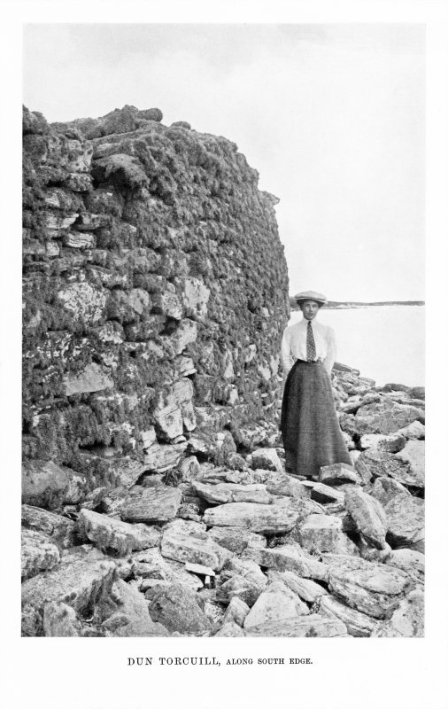 North Uist, Dun Torcuill. View of broch wall along south edge. Women standing in view. Photograph copied from 'North Uist' by Erskine Beveridge.