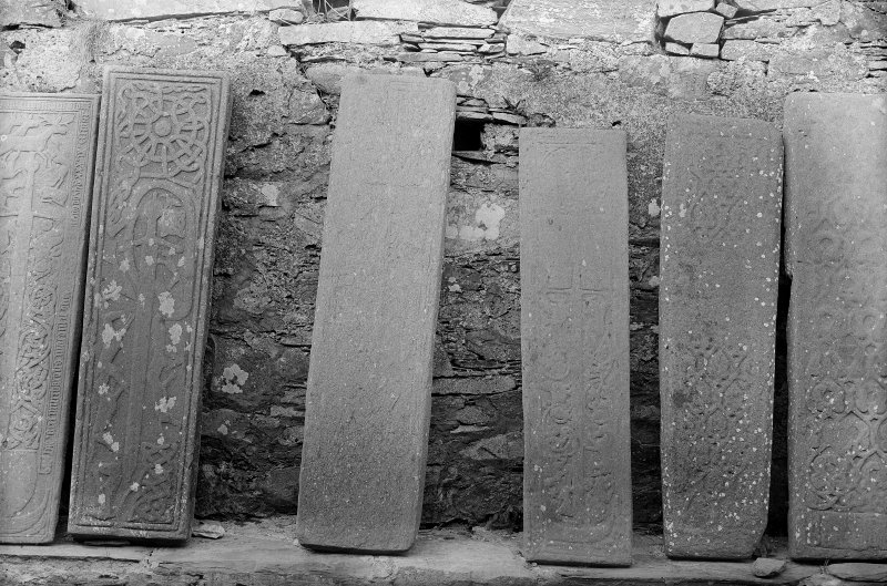 Oronsay Priory, interior, grave-slabs. General view of a number of grave-slabs lined up along wall.