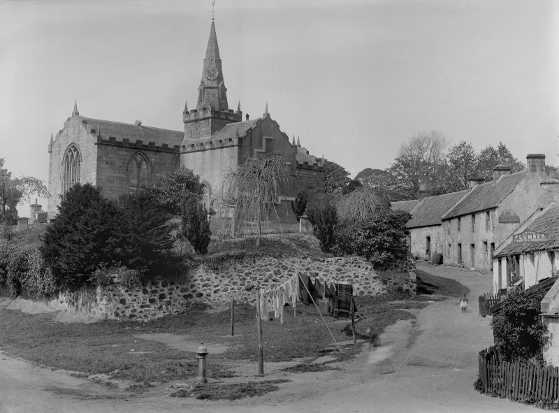 View of Largo Parish Church and churchyard, cottages and sign for a 'plumber' from the east.
