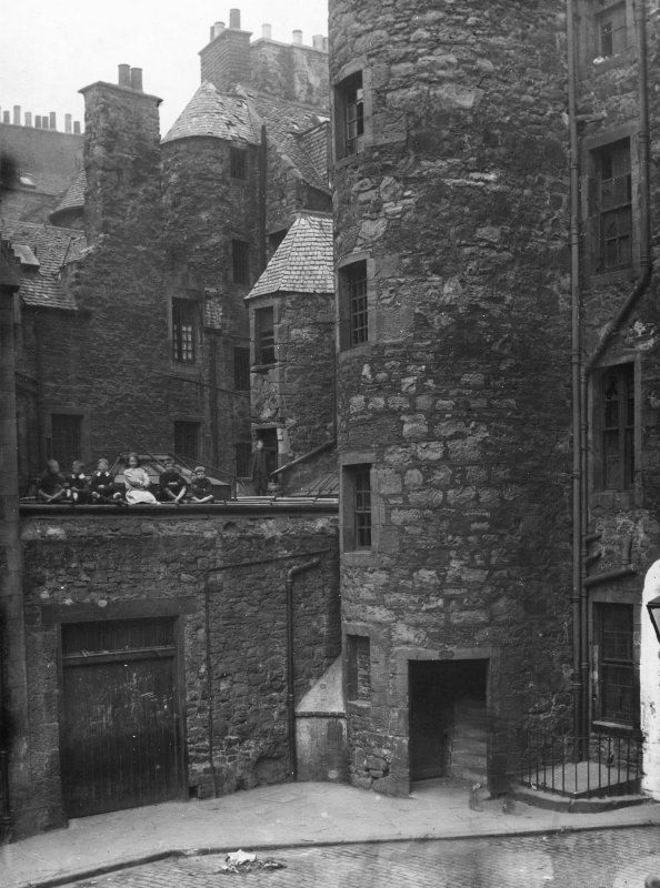 View of North West corner of St John Street, Edinburgh, with children sitting on the roof. This area was covered in after 1877 and before 1894. This area is now an open courtyard. Also showing Smollet ...
