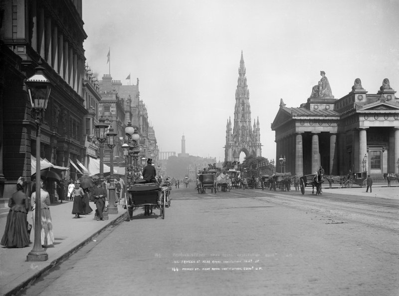 View of Princes Street, Edinburgh from west showing a busy street with horse-drawn vehicles; carts, carriages and buses.  View also includes Scott Monument and Royal Scottish Academy.   Titled: 'PRINCES ST.  NEAR ROYAL INSTITUTION. EDINR J.P.'