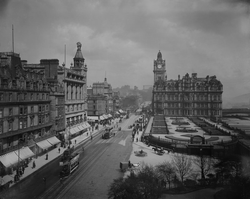 View from Scott Monument looking east towards Calton Hill showing the North British Hotel, Waverley Gardens and a busy Princes Street with shop awnings, pedestrians, trams and horse drawn vehicles.