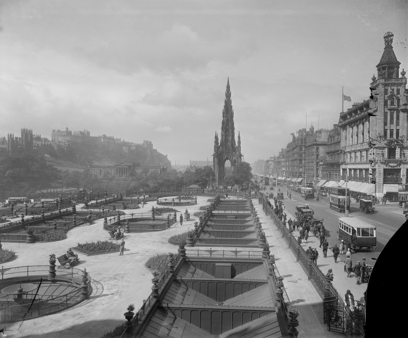 General view of Princes Street looking westwards showing the Castle, Mound, Scott Monument, Waverley Gardens and a busy street with trams, pedestrians and cars.