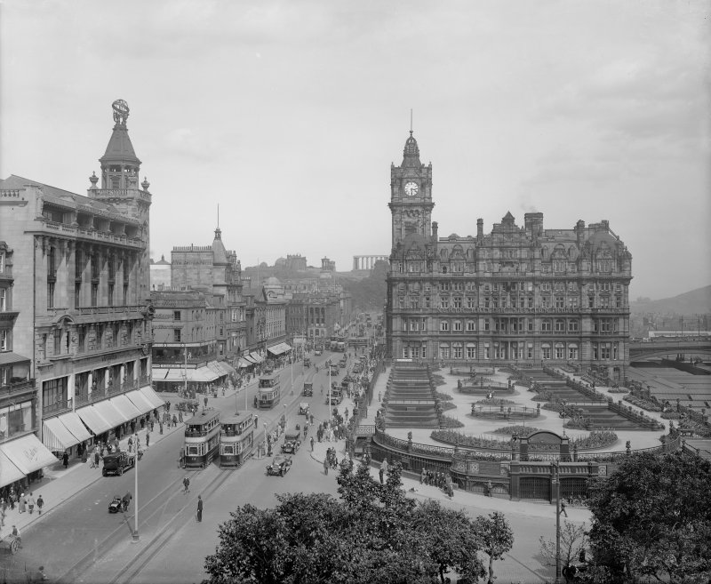 View looking east from Scott Monument towards Calton Hill showing the North British Hotel and Waverley Gardens and a busy Princes Street with shop awnings, trams, cars and pedestrians.