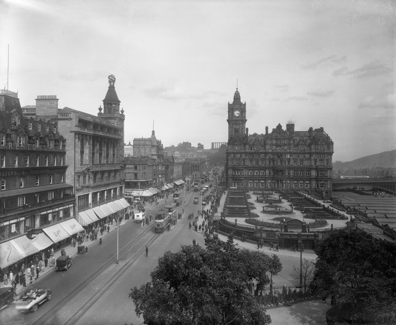 General view of Princes Street from Scott Monument to the east showing the North British Hotel, Waverley Gardens, Calton Hill and a busy street with pedestrians, trams and cars.