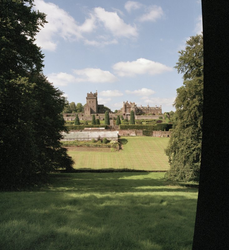 Distant view of keep, mansion and garden from South.
