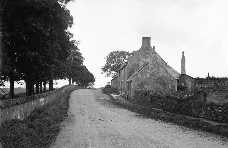 View of unidentified cottages and adjacent industrial building with chimney. Probably in Fife.
