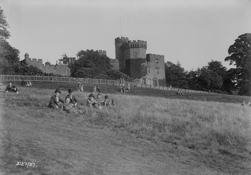 General view of Balloch Castle with people sitting on the bank below.