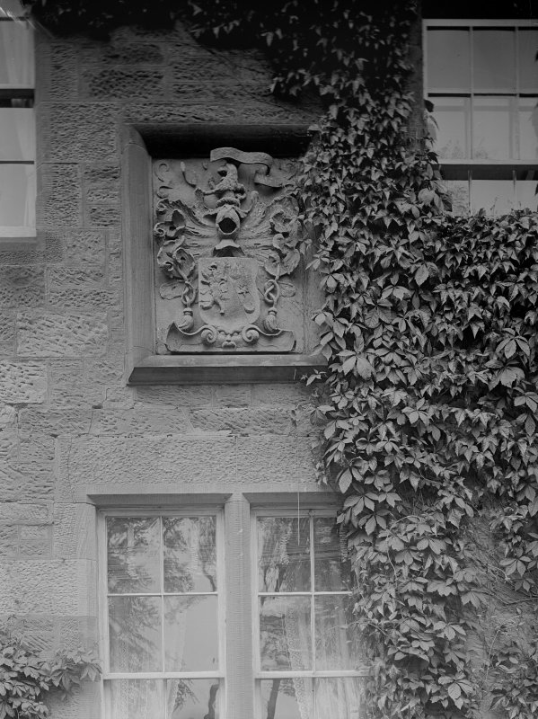 Detail of heraldic stone in wall of farmhouse.