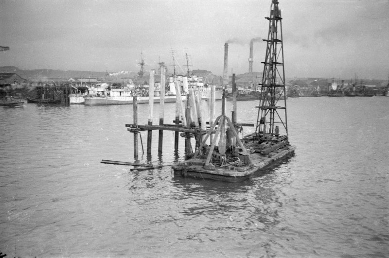 Scanned image of negative showing temprary pontoon with drilling barge alongside in main basin with destroyers in the background, taken from the SE.
