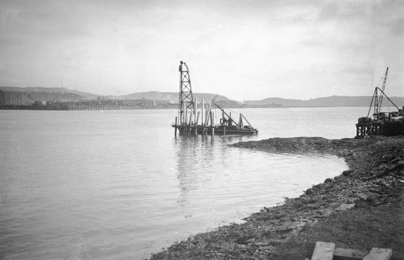 Scanned image of negative showig N wall with a pontoon and drilling barge in the foreground, taken from the SW.