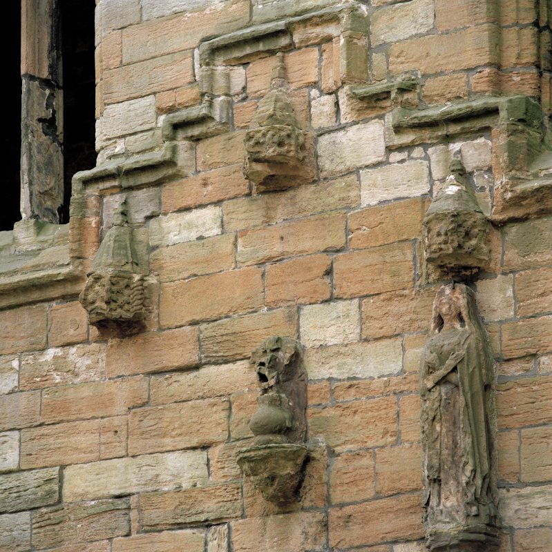 Courtyard, south facade, carving over entrance, detail of central canopy and corbel