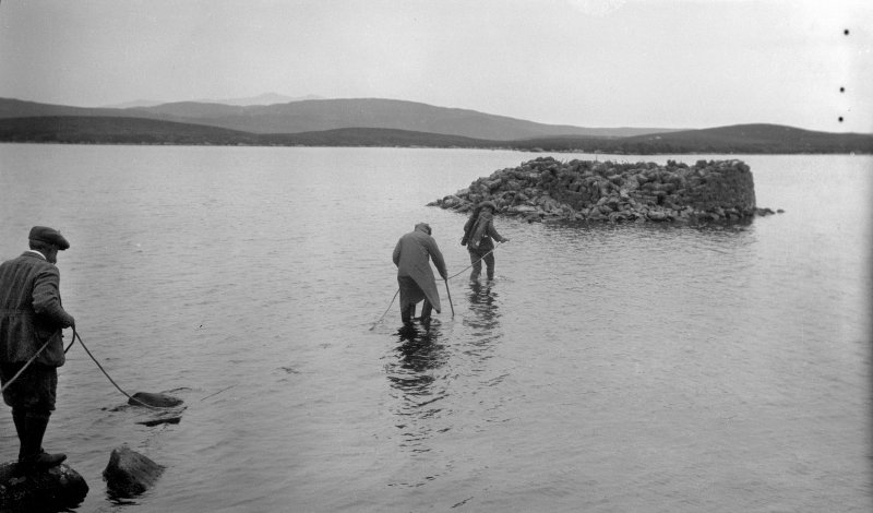 View of RCAHMS surveyors wading out to a dun in 1924, Dun Nighean Righ Lochlainn, North Uist. Research indicates that they inlcude G P H Watson (middle) with a local ghillie on the right.