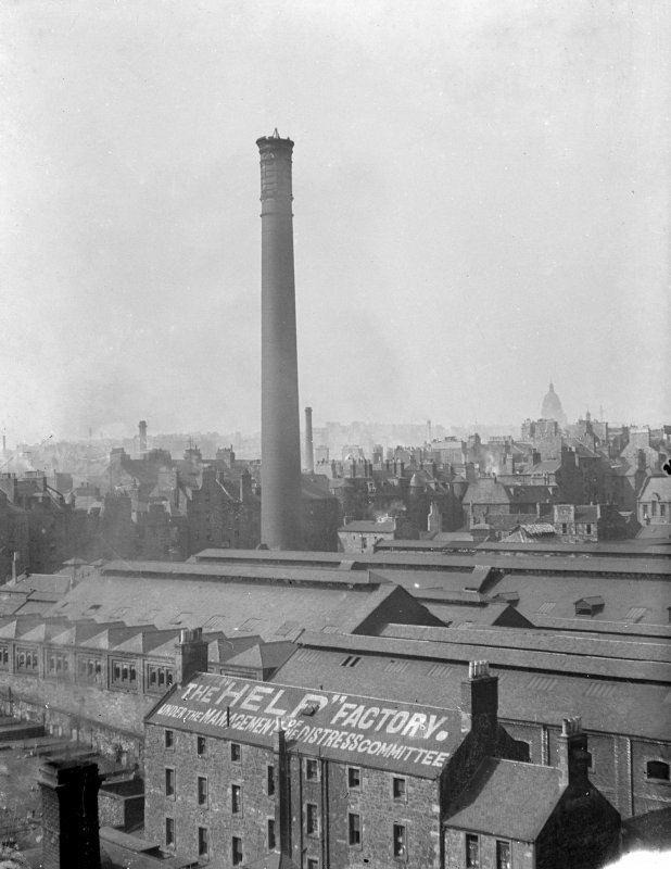"General view of Canongate, looking towards Gasworks chimney, with factory in foreground with writing on roof which reads ""The ""Help"" Factory. Under the Management of the Distress Committee"""