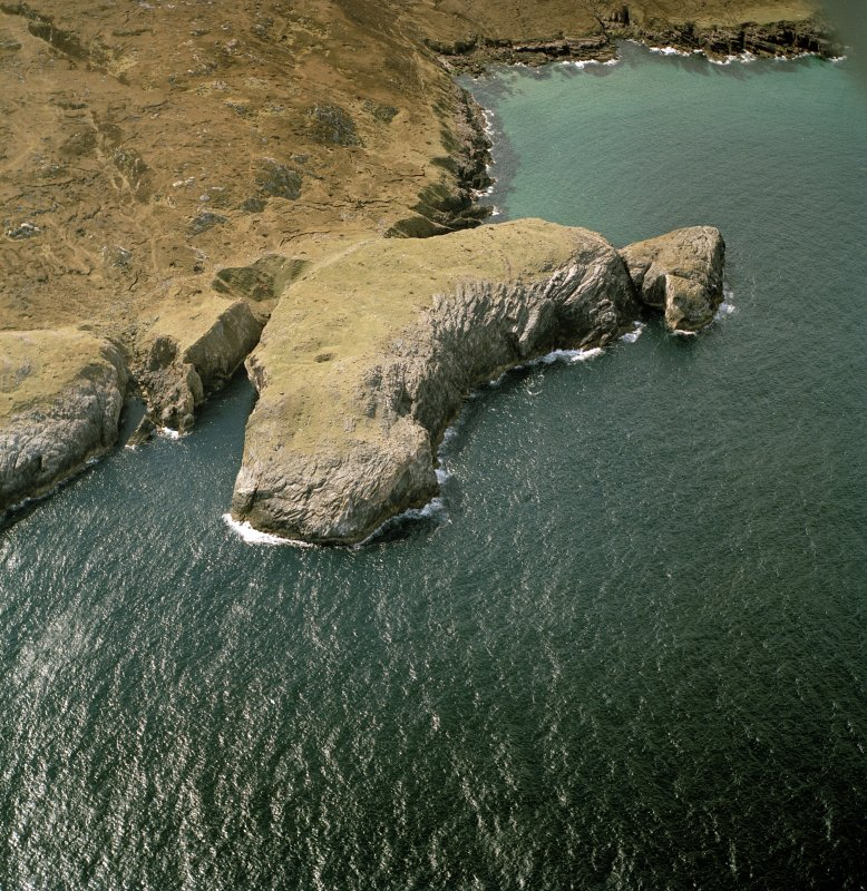 Oblique aerial view centred on the remains of Eilean Nan Caorach fort, taken from the NE.