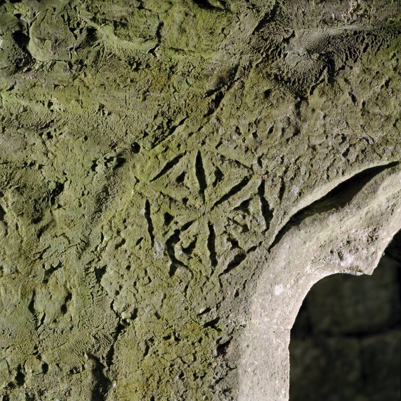 Detail of incised carving over window at E end in S wall.