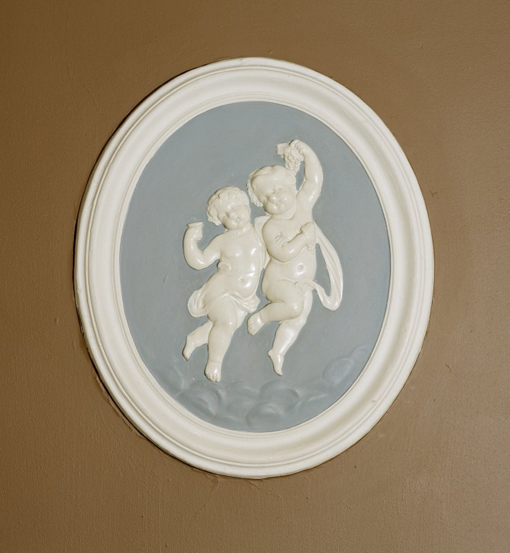 Interior. Entrance hall, detail of oval wall plaque with putti