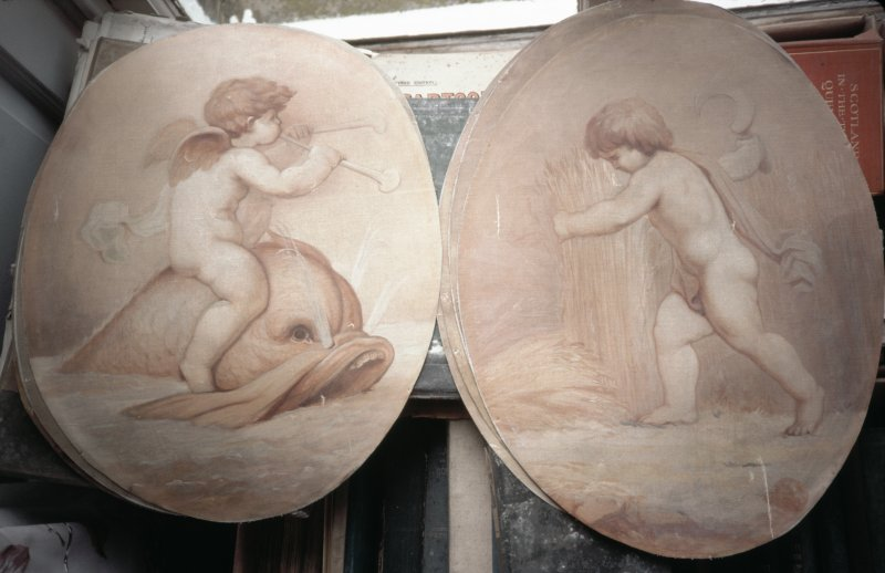 Painted oval panels: cherub on sea-creature and cherubs scything.