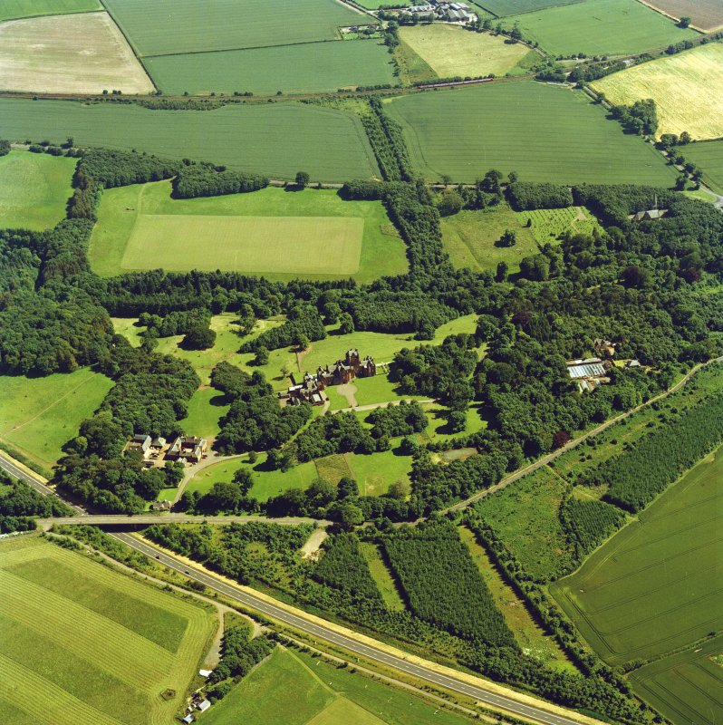 Oblique aerial view centred on the country house, with the farmsteading, the gate-lodge, the burial ground and the church adjacent, taken from the NNW.