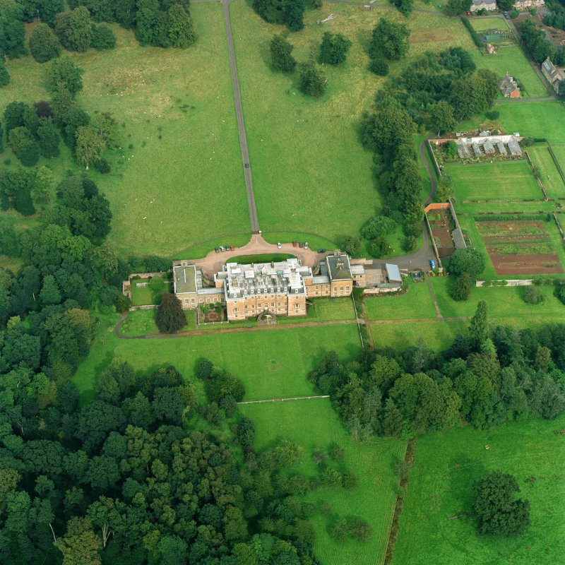 Oblique aerial view centred on the country house with walled garden adjacent, taken from the SW.