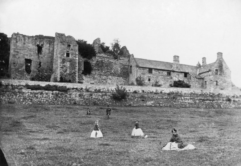 General view of South elevation of Aberdour Castle with people in foreground.