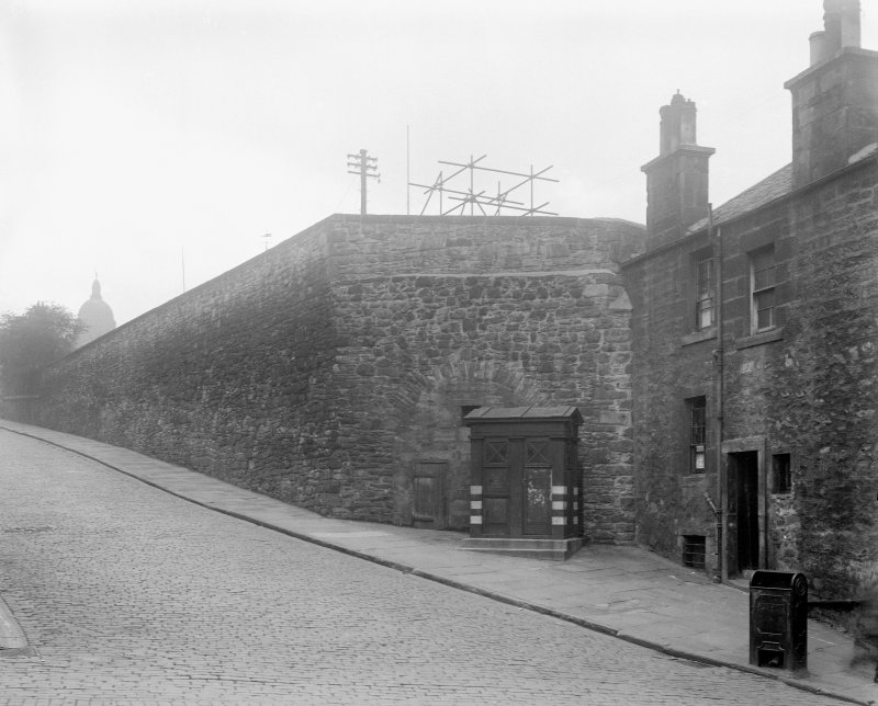 View of the Flodden Wall on Drummond Street seen from the Pleasance from the East. The South facade of No. 31a Pleasance can be seen along with a Police Box.