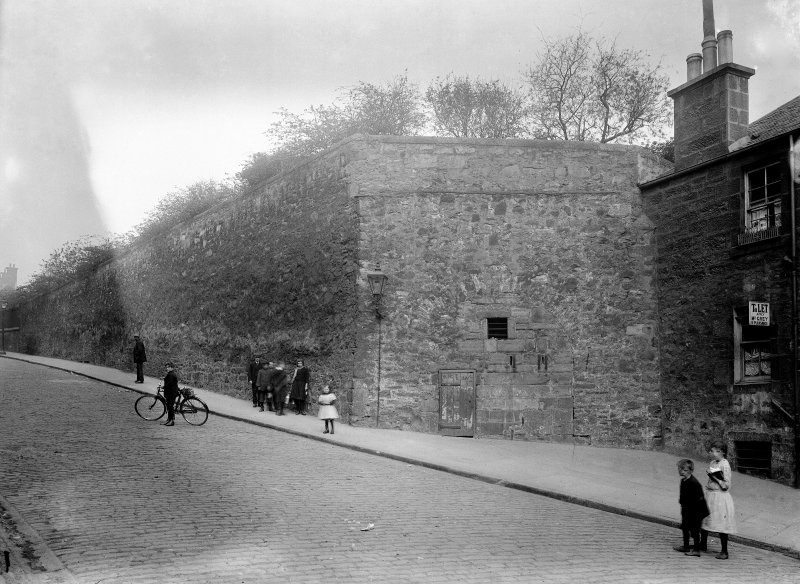 View of the Flodden Wall in Drummond Street seen from the Pleasance from the East. The South facade of No. 31a Pleasance can be seen along with children playing.
