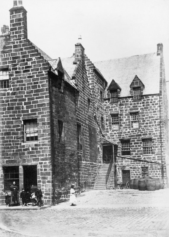 "View of houses with family group standing outside. Titled: 'The Place of Paisley.' Inscribed on verso; 'In its latter days it became a pub and a low tenement. It is now the Session House of Paisley Abbey. The residence of the Cochranes of Dundonald. Here Jean Cochran was married to John Graham Duke of Claverhouse, ""Bloody Claverhouse"". He was killed at Killiecrankie. She afterwards married and was killed with her infant son in Holland. Their bodies were discovered in perfect preservation in Kilsyth Old Aisle two hundred years later. See the book ""My Lady Dundee"" for details. [Used in Gardner, Alexander ""A handbook to Paisley,""and in Rowand, David ""Pictorial history of Paisley,"" (1993) where it is said to have been restored c1912.]"