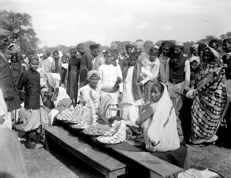 Group gathered around sweet seller on the Maidan, Kolkata.  The group includes non Bengalis, possibly visiting for a festival.