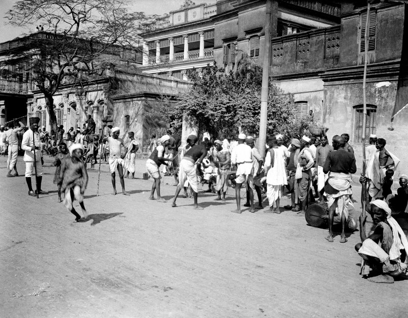Street scene with possible game or betting with watching policeman, probably Kolkata.