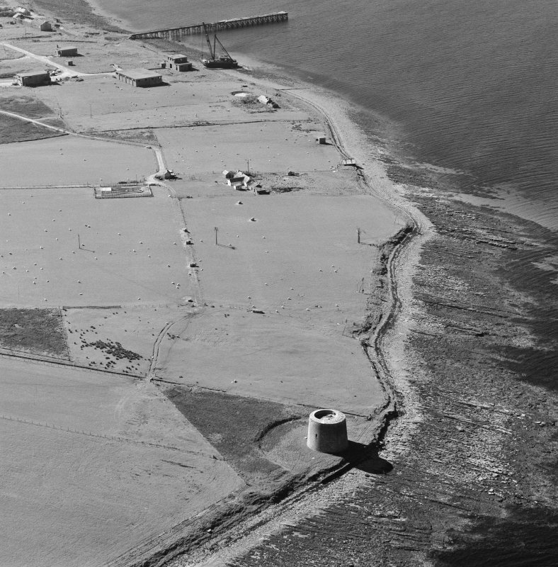 Oblique aerial view of Orkney, Hoy, Crockness Martello Tower, taken from the S.  Also visible is part of the Second World War Rinnigil barrage balloon gas production plant.