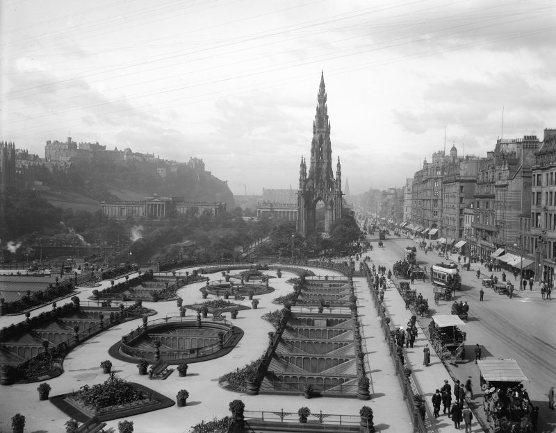 General view of Princes Street, Edinburgh, looking westwards showing the Castle, Mound, Scott Monument, Waverley Gardens and a busy street with trams, pedestrians and horse drawn buses and carriages.