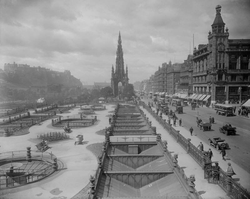 Historic view of Princes Street, Edinburgh showing Waverley Gardens and Scott Monument, trams, horse-drawn and motor traffic and pedestrians.