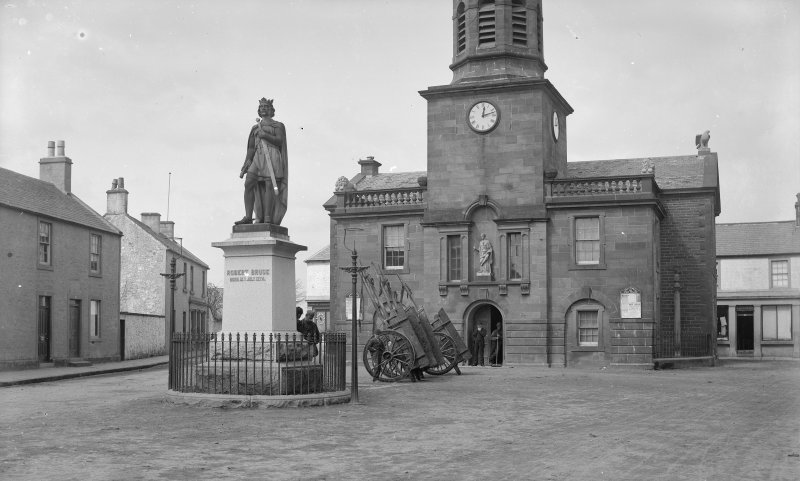 View from S of town hall and statue of Robert Bruce, High Street, Lochmaber. Large carts are balanced end on behind the statue.