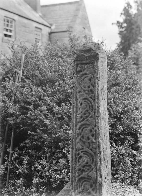 Detail of cross shaft in grounds with house in background.