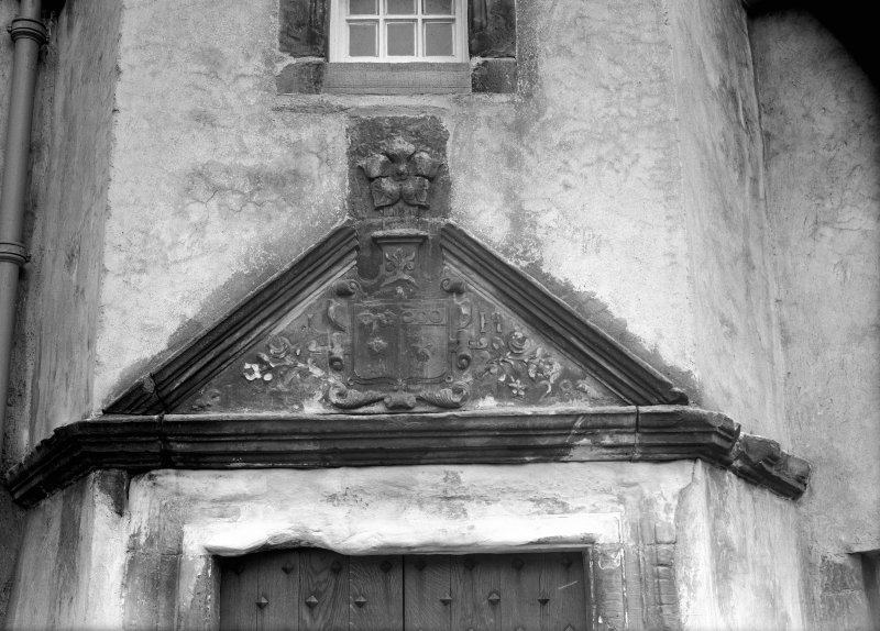 Detail of pediment with armorial panel above entrance doorway of corner tower.