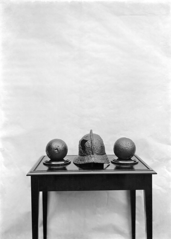Photograph of 16th - 17th century helmet and 2 cannonballs displayed on table