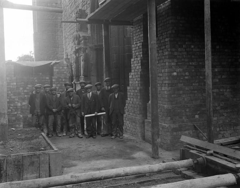 Interior. View of bricklayers and masons in crossing.