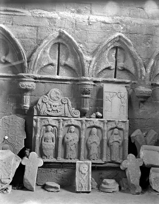 Historic photograph showing detail of tombstones and stone sculpture in sacristy.