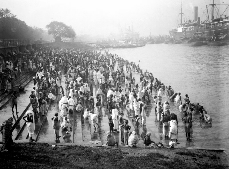 Crowded riverside with bathers, Chandpal Ghat, Kolkata.  Bathers reached the river through tunnels under the railway line.