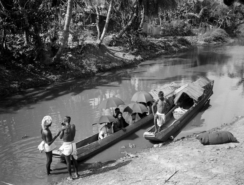 Group seated in two ferry canoes moored in stream.  Unknown location.