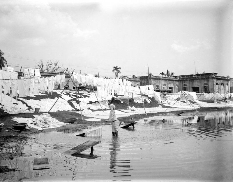 Waterside with washerman and washing lines at a dhobi ghat.  Unknown location.