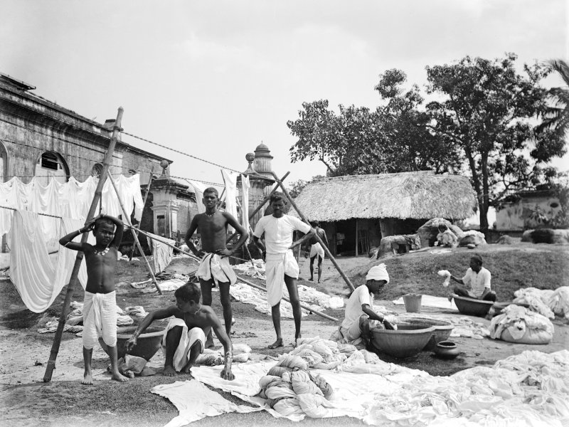 Waterside with group of washermen at a dhobi ghat.  Unknown location.