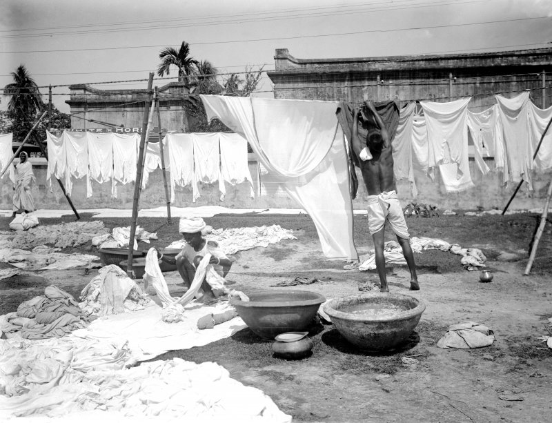 Washermen on waterside at a dhobi ghat, with 'White Horse' (likely whisky advertisement) sign in the background.  Unknown location.