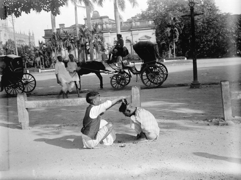 Street hairdresser giving a 'Hindustani haircut' (pudding bowl), Strand Road South, Kolkata.  The High Court is in the left distance, the building behind could be the Volunteer HQ.