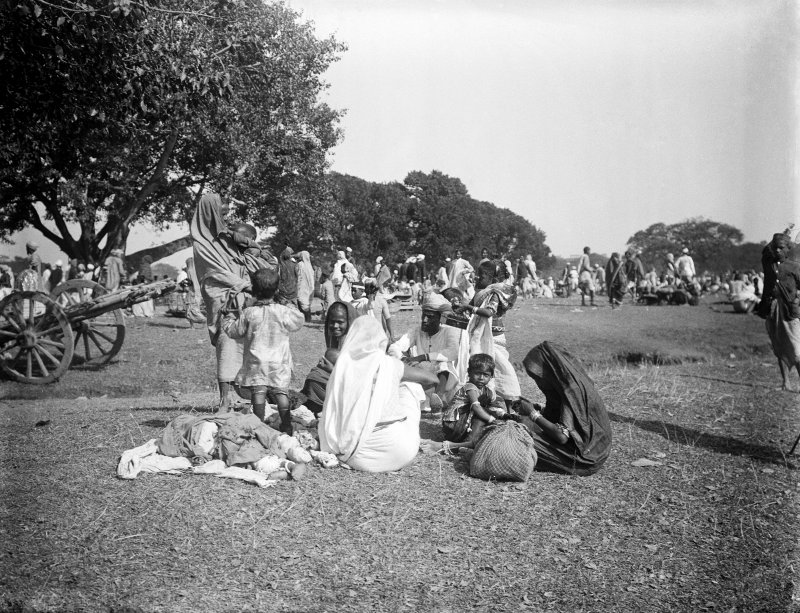Seated family group, possibly on the Maidan, Kolkata.  The group may be pilgrims to a festival from outside Bengal.